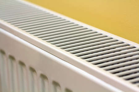Photo for Close-up of white heating radiator detail on light yellow wall copy space background. Comfortable warm home interior, climate control concept. - Royalty Free Image