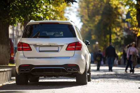 Photo pour Back view of white car parked on city pedestrian zone on background of blurred silhouettes of people walking along green sunny summer alley. Modern city lifestyle concept. - image libre de droit