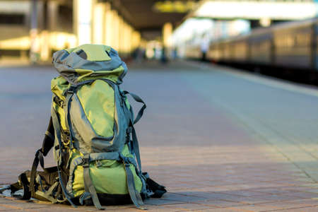 Close-up of big green tourist backpack on railway station platform on blurred background. Traveling, adventure and recreation concept.