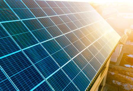Photo pour Close-up surface of lit by sun blue shiny solar photo voltaic panels. System producing renewable clean energy. Renewable ecological green energy production concept. - image libre de droit