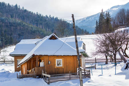 Photo pour Beautiful cozy one-story wooden ecological comfortable traditional residential cottage houses with terrace, attic room and steep roof covered with snow on mountain slope on sunny cold winter day. - image libre de droit