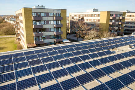 Photo for Aerial view of blue shiny solar photo voltaic panels system on commercial roof producing renewable clean energy on city landscape background. - Royalty Free Image