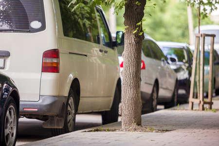 Foto de Cars parked on a city street on summer day. - Imagen libre de derechos
