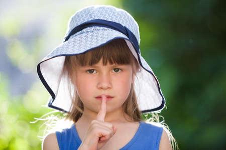 Foto de Close-up portrait of serious little girl in a big hat. Child having fun time outdoors in summer. - Imagen libre de derechos