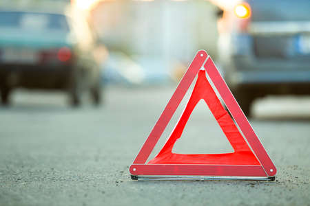 Photo pour Red emergency triangle stop sign and broken car on a city street. - image libre de droit