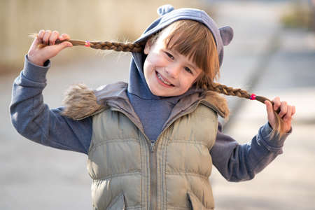 Foto de Portrait of happy child girl with hair braids in warm clothes in autumn outdoors. - Imagen libre de derechos