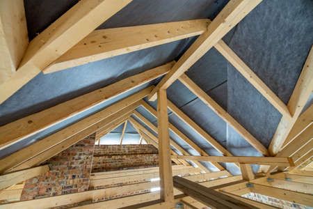 Photo pour Attic space of a building under construction with wooden beams of a roof structure and brick walls. Real estate development concept. - image libre de droit