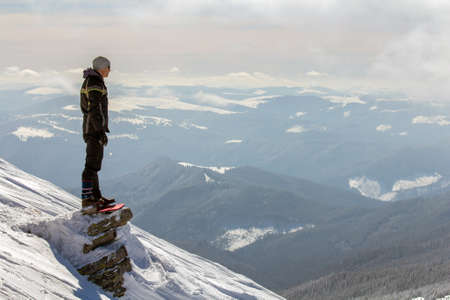 Photo pour Silhouette of alone tourist standing on snowy mountain top enjoying view and achievement on bright sunny winter day. Adventure, outdoors activities and healthy lifestyle concept. - image libre de droit