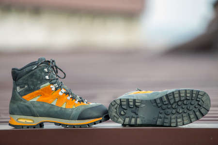 Photo for A pair of leather trekking hiking winter boots on blurred background - Royalty Free Image