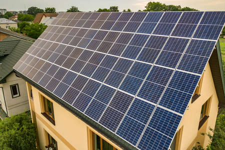 Photo for Aerial top view of new modern residential house cottage with blue shiny solar photo voltaic panels system on roof. Renewable ecological green energy production concept. - Royalty Free Image