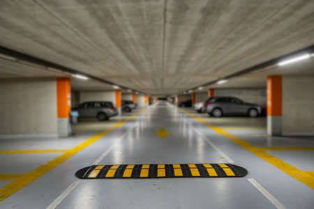 Photo for Yellow markings with blurred modern cars parked inside closed underground parking lot. - Royalty Free Image