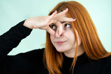 Photo pour Funny pretty redhead girl showing bad smell sign with her fingers. - image libre de droit