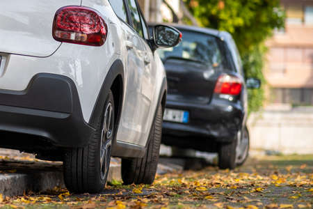 Photo for Modern cars parked on city street side in residential discrict. Shiny vehicles parked by the curb. Urban transportation infrastructure concept. - Royalty Free Image