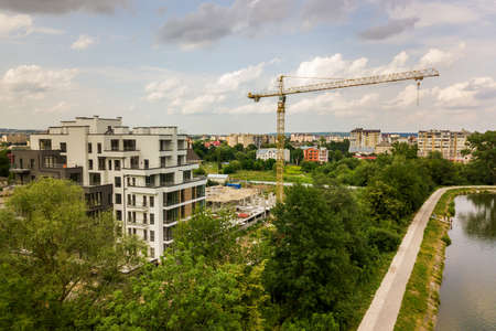 Photo pour Aerial view of tower lifting crane and concrete frame of tall apartment residential building under construction in a city. Urban development and real estate growth concept. - image libre de droit