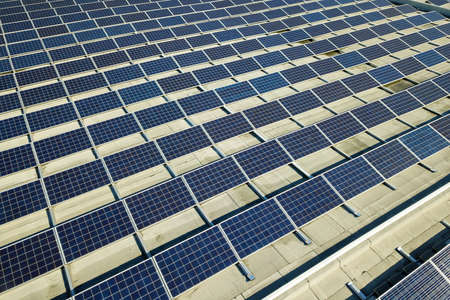 Photo pour Aerial view of many photo voltaic solar panels mounted of industrial building roof. - image libre de droit