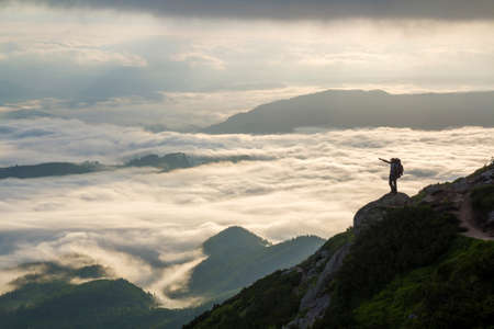 Photo for Wide mountain panorama. Small silhouette of tourist with backpack on rocky mountain slope with raised hands over valley covered with white puffy clouds. Beauty of nature, tourism and traveling concept - Royalty Free Image