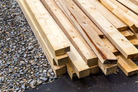 Photo pour Stack of natural wooden boards on building site. Industrial timber for carpentry, building or repairing, lumber material for roofing construction. - image libre de droit