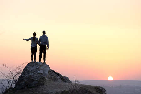 Photo for Man and woman hikers standing on big stone at sunset in mountains. Couple on high rock in evening nature. Tourism, traveling and healthy lifestyle concept. - Royalty Free Image