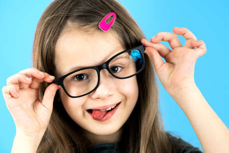 Photo pour Close up portrait of a funny child school girl wearing looking glasses isolated on blue background. - image libre de droit