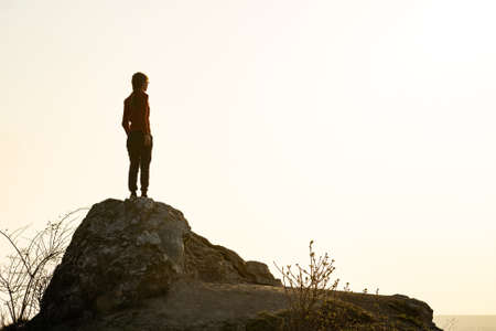Photo pour Young woman hiker standing alone on big stone in morning mountains. Female tourist on high rock in wild nature. Tourism, traveling and healthy lifestyle concept. - image libre de droit