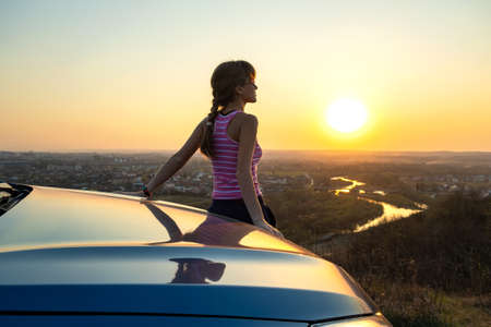 Photo for Young woman driver standing near her car enjoying warm sunset view. Girl traveler leaning on vehicle hood looking at evening horizon. - Royalty Free Image