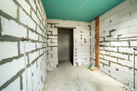 Photo pour Interior of an apartment room with bare walls and ceiling under construction. - image libre de droit