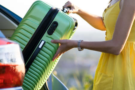 Photo pour Female driver in summer dress putting green suitcase inside her car trunk. Travel and vacations concept. - image libre de droit