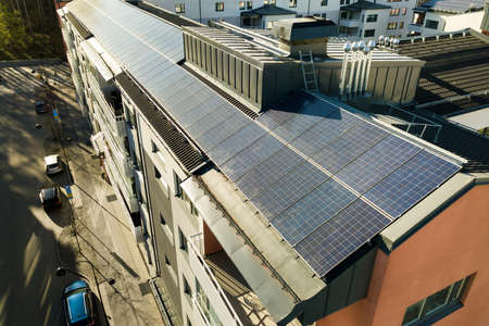 Photo for Aerial view of solar photovoltaic panels on a roof top of residential building block for producing clean electric energy. Autonomous housing concept. - Royalty Free Image