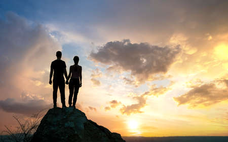 Photo for Man and woman hikers standing on a big stone at sunset in mountains. Couple together on a high rock in evening nature. Tourism, traveling and healthy lifestyle concept. - Royalty Free Image