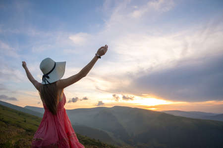 Foto de Young woman in red dress standing on grassy field on a windy evening in autumn mountains raising up her hands enjoying view of nature. - Imagen libre de derechos