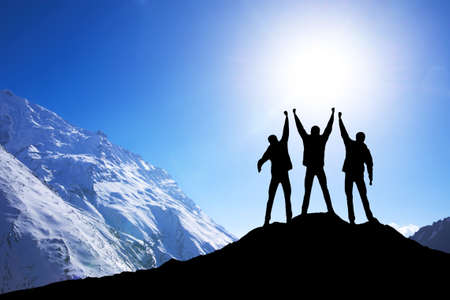 Silhouette of team on mountain peak. Sport and active life concept