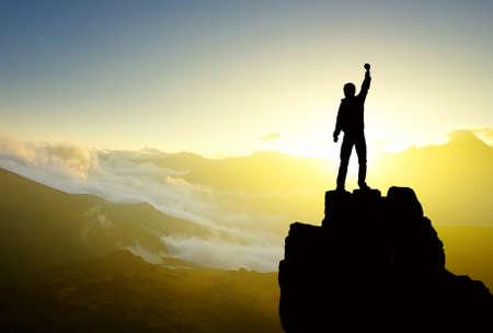 Foto de Winner silhouette on mountain top. Sport and active life concept - Imagen libre de derechos