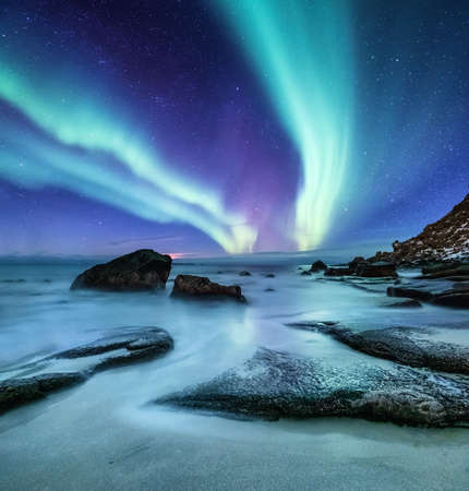 Foto de Aurora borealis on the Lofoten islands, Norway. Green northern lights above ocean shore. Night sky with polar lights. Night winter landscape with aurora and reflection on the water surface. Natural background in the Norway - Imagen libre de derechos