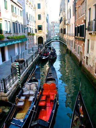 Brightly colored gondolas in a narrow Venice waterway