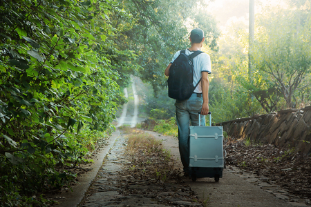 Photo pour A young man carrying luggage on a mountain road - image libre de droit