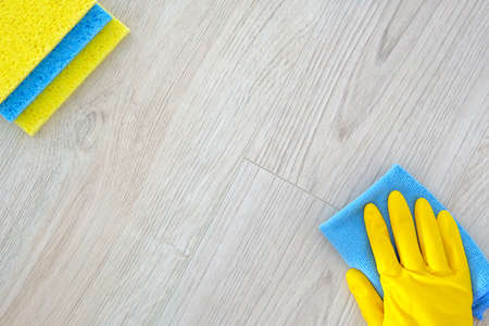 Foto de Flat lay cleaning products, copy space. Hand in yellow rubber protective glove with micro. Service concept. Top view. - Imagen libre de derechos