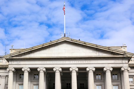 US Treasury Department Front Columns and Flag Pennsylvania Ave Washington DC.  The Treasury is located next to the White House because President Andrew Jackson told his advisors that he wanted the National Bank to be right there where he could see it.