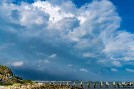 Photo pour Storm Coming Beach Pier Buzzards Bay Ocean Padanaram Dartmouth Massachusetts New Bedford and Fort Rodman in distance - image libre de droit