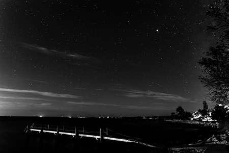 Photo pour Black and White Night Stars Beach Pier Buzzards Bay Ocean Padanaram Dartmouth Massachusetts Lights in distance - image libre de droit