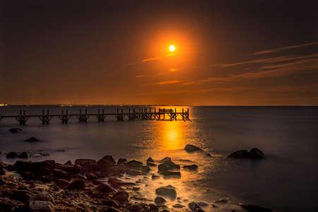 Photo pour Moon  Rising Night Stars Beach Pier Buzzards Bay Ocean Padanaram Dartmouth Massachusetts New Bedford Lights in distance - image libre de droit