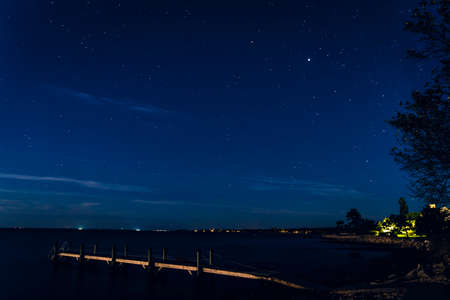 Photo pour Night Stars Beach Pier Buzzards Bay Ocean Padanaram Dartmouth Massachusetts Lights in distance - image libre de droit