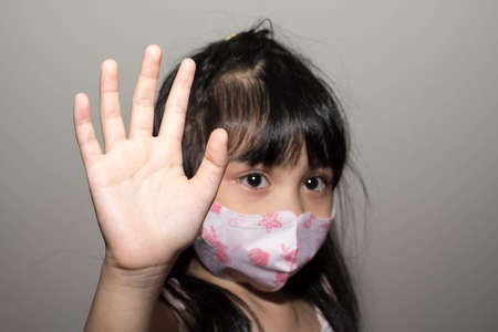 Photo for Kids hand to say no against corona virus infection. Blurry image of a female kid showing her hand to symbolize against the spread of corona virus - Royalty Free Image