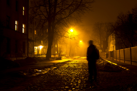 Photo for One man on the foggy street at night - Royalty Free Image