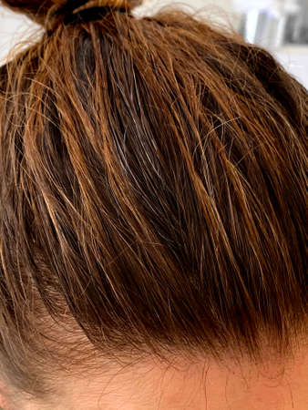 Photo pour The top of a young woman's head with some new gray hairs showing - image libre de droit
