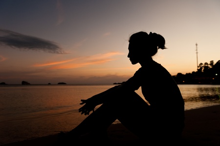 Silhouette woman sitting on the beach looking out to sea