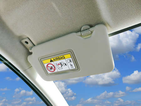 Photo pour Car sun visor and warning signs of airbag system in car with sky and clouds as a backdrop. - image libre de droit