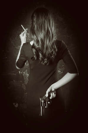 Black and white portrait of dangerous young woman back with long hair, dark dress. She takes gun in her hand