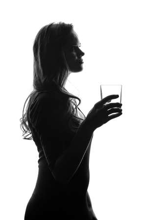 Photo pour Silhouette of handsome woman with long hair with glass in her hand. She stays side to camera and looks stright. Cut-out scene. Studio shot - image libre de droit