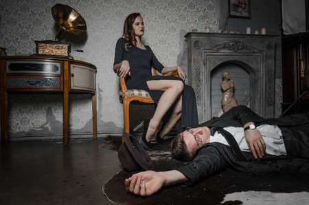 Film scene. Femme Fatale committed murder. Beautiful woman sits near dead body of detective. Body of man lying on floor. Woman holding glass of whiskey