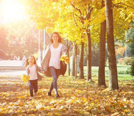 Happy time family and love abstract: mother and daughter run in autumn park, yellow tree